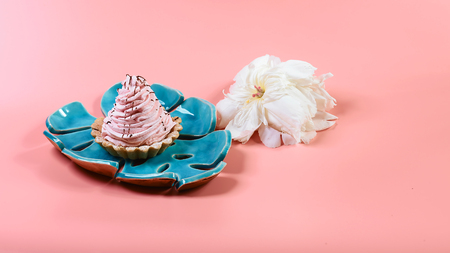 delicious dessert on a blue decorative plate, pink and white flowers pions on a pink background, copy space, Flat lay. Stockfoto