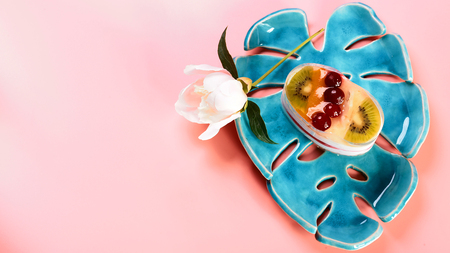 cheesecake with fruit dessert on a decorative plate, flowers on a pink background, copy space, Flat lay.
