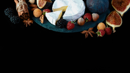 camembert or brie cheese with figs and berries of blackberries and raspberries on a shale board isolated on a black background, Flat lay, Copy space.
