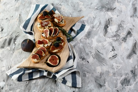 set bruschettas with figs, cheese, honey and walnuts on grilled crusty bread on a wooden board insulated on a black background. Flat lay, Free space for text. Foto de archivo - 107568218