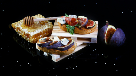 Presentation on wooden stand bruschetta with figs, blue cheese, honey and prosciutto Isolated on black background. Flat lay, Copy space. Stock Photo