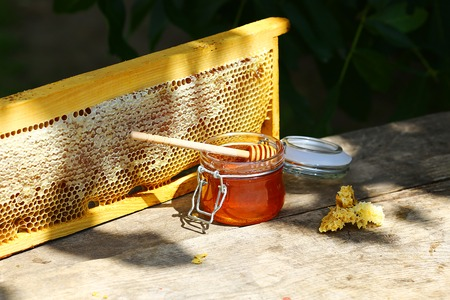 jar of fresh honey in a glass jar on an old table on a apiary. outside. frame with bees wax structure full of fresh bee honey in honeycombs. Beekeeping concept. Top view. Copy space. 免版税图像