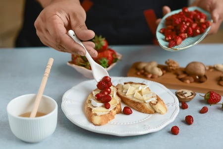 Sweet sandwiches with strawberries, cheese, camembert, brie, nuts and honey on the bruschetta cooking by chef hand on light background. Stockfoto