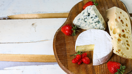 Cheese Assortment Board: Camembert or Brie, Dourble, Maasdam and strawberry in rural wooden surface. Authentic lifestyle image. Top view. Copy space.