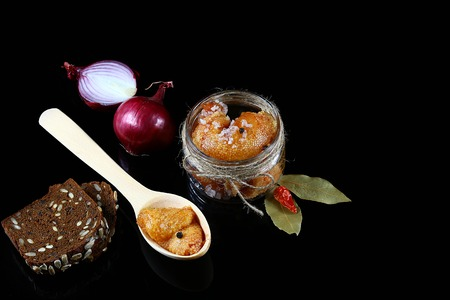 Gourmet food Pike caviar, roe in a glass jar, red hot pepper, laurel leaves, wooden spoon of fish caviar on a black background, Flat lay. Copy space. Banco de Imagens