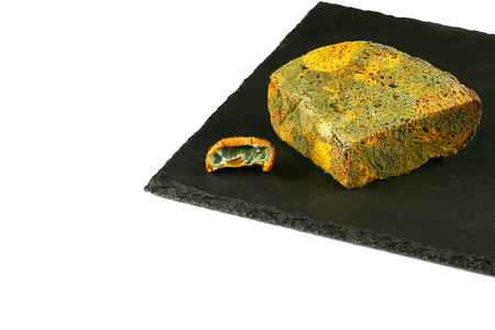 piece of black bread with green mold and a piece of kiwi with a mold on a black shale board isolated on white background, concept of inedible products, place for text, Flat lay.