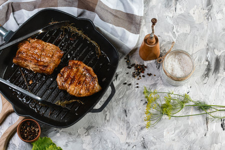 Juicy thick grilled beef steak seasoned with rosemary fresh o viewed from above in a close up view . Banco de Imagens