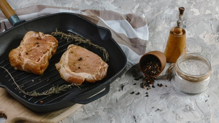Raw meat Ribeye steak, on cast iron frying pan on wooden background with rosemary fresh o viewed from above in a close up view.