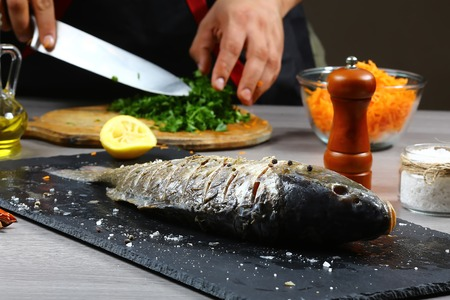 cuts parsley be chef hands and cooking fresh fish with seasoning on a shale board on wooden table flat top view, copy text menu. Фото со стока