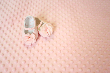 Baby newborn pink background, vintage newborn shoes for baptism on soft texture background , blank space for message.