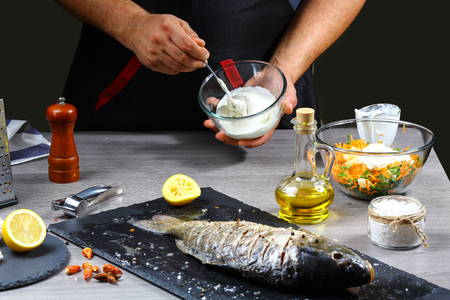mens hands, close-up, holding fish sauce, Chef cooks fish. healthy food, diet or cooking concept
