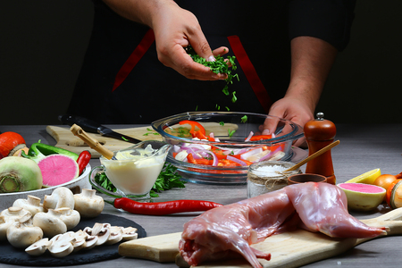Professional chef cooking rabbit meat baked with vegetables on a dark background. service photo background. Horizontal view. selective focus