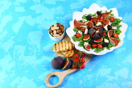 figs salad with lettuce cheese and nut on ceramic plate blue background. top view copy space. Banque d'images