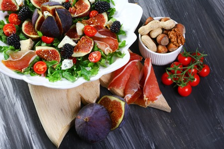 Salad with figs, blue cheese, arugula, prosciutto and walnuts on wooden background, top view. Stock Photo