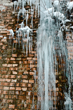 icicles, ice build-up on the background of a brick wall, closeup abstract old brick wall background with crack ice and moss.