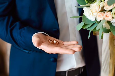 The bridegroom is holding a gold wedding rings in her hand. A bridegroom with a bouquet at the wedding. The concept of weddings and the style.