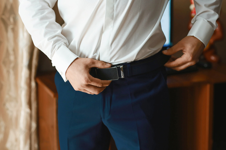Groom holding hands on the belt, wedding suit. Stock Photo