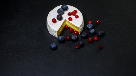 An overhead photo of Camembert cheese with berries cranberries and blueberries, shot from above on shale board background with copy space.
