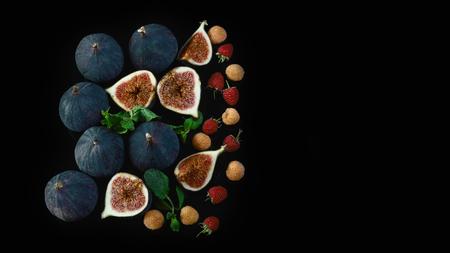 Fresh figs and raspberry berries with mint leaves on a black background. copy text. Flat lay. Banque d'images