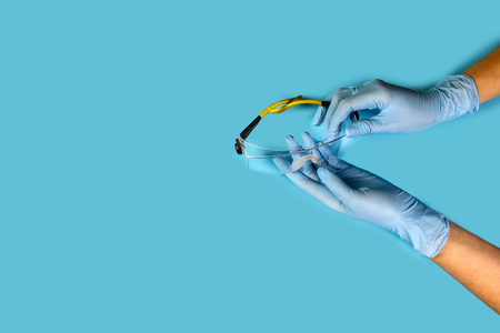 master nails in blue gloves hold protective glasses. Composition for card with a place for text. Archivio Fotografico