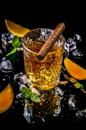 Elite drink for masculine relaxation glasse of whiskey and and cigar, ice cube on black background, copy space. concept luxury drink.