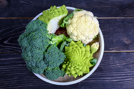 Collection of Romanesco broccoli and cauliflower on the kitchen table. Low-calorie nutritional products. Banco de Imagens