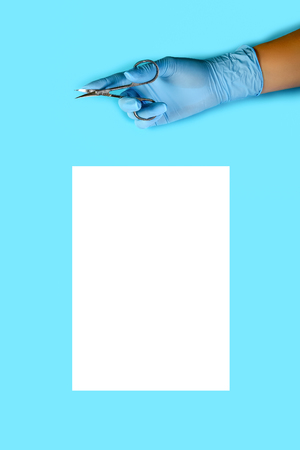 master nails in blue gloves holds manicure scissors. sheet of white paper. manicure accessories on blue background top view. Composition for card with a place for text.