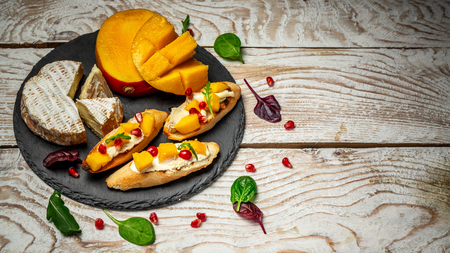 Top view of Bruschetta with sweet mango and cheese. on a light wooden background. Healthy food.
