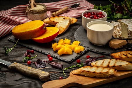 Ingredients for sandwiches with ricotta, mango, cranberry on a dark wooden background, Flat top view. copy space. Stok Fotoğraf