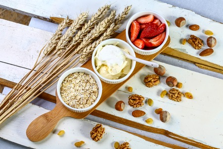 Breakfast with oatmeal, yogurt, strawberries, nuts on white background. Healthy food concept. Flat lay top view Фото со стока