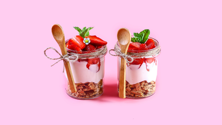 Summer dessert, classic cheesecake with strawberries decorated with mint leaves. Isolated on pink background, copy space. 免版税图像