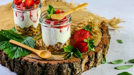 Strawberry parfait. Delicious dessert jars with a rustic wood background.