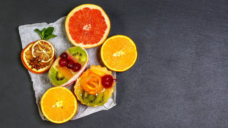healthy food beautiful and tasty fruit isolated on dark background, shale board. top view, space for text.