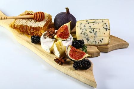 Cheese plate with blue cheese, brie, truffle hard cheese with grapes, figs, honey, dried fruits and nuts on white table. Top view. Copy space.