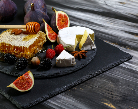 White cheese brie or camembert. Gourmet appetizer cheese plate with white cheese, figs, honey, raspberry and blackberries. 写真素材
