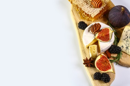 Cheese plate served with berries, figs, and nuts on a wooden background. Top view. Copy space.