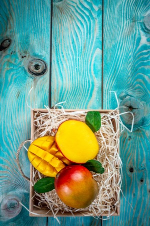 Fresh mango organic product in wooden box. Blue background. Top view. Copy space. vertical image. 免版税图像