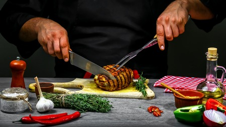 Cooking meat steak, vegetables and spices with by chef hands on wooden background. Food recipe concept.