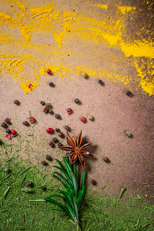 Spicy background with assortment of different hot chili, thyme, anise, pepper peas, in the form of a flowerall, mix spices. Top view. space for text. Standard-Bild - 116369933