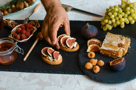 Toasts of cheese, figs and honey on whole-grain crispy bread. Close up. concept of Italian cuisine.
