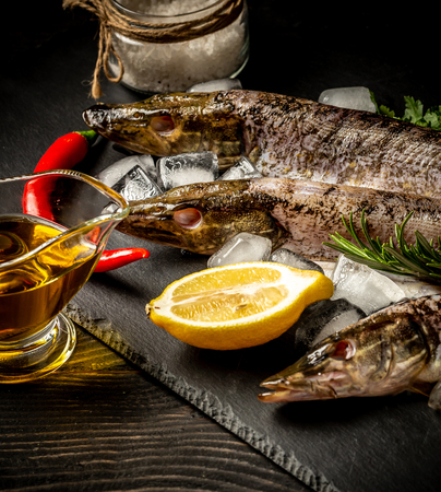 Chilled fish pike on a plate with ice and lemon. Food background. Top view with copy space. Stock Photo