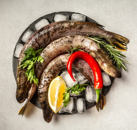 Delicious fresh fish on vintage background. Fish with aromatic herbs, spices and vegetables - healthy food, diet or cooking concept. with space for text top view. Stock fotó