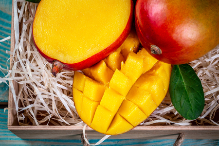 Close-up mango fruit with sliced diced mango chunks on a wooden background, top view.