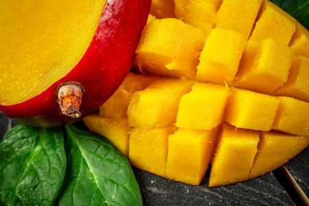 Close-up Mango fruit and mango cubes on a wooden background, top view. Banque d'images