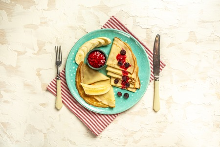 Crepes with fresh berries on rustic wooden background with space for text, top view. Pancake. sweet breakfast. food recipe.