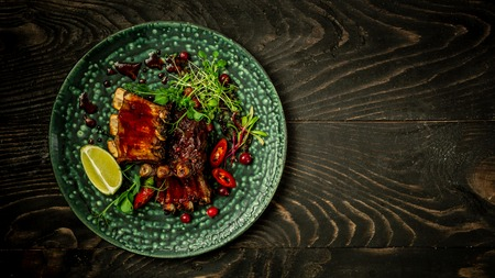 Beef Short Ribs with a spicy berry sauce and served with green seedlings on the plate. Shallow Depth of Field. concept of Asian cuisine. restaurant serving. top view, place for text.