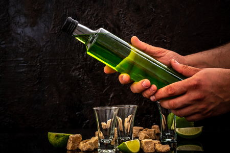 bottle of absinthe in the hands of bartender. lime slices, cube brown sugar on dark background. free space for text. the concept of elite alcohol. Фото со стока