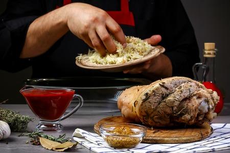 Kochhände bereiten Schweinshaxe vor. Cook bereitet köstliche Schweinshaxe mit Bierzugabe zu. Bayerisches Kochrezept.