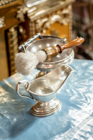 Tools for baby baptism. sacred water in the bowl. Bunch of consecration. Catholicism, the concept of Christianity. Stock Photo