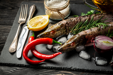 Raw river fish with lemon slices, herbs rosemary, salt and pepper on dark background. Healthy food and diet concept. Top view, copy space. Ingredients for cooking fish.